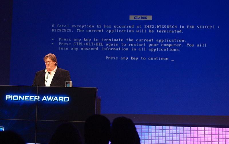 Gabe Newell faisant une présentation avec un écran bleu humoristique de la mort derrière lui